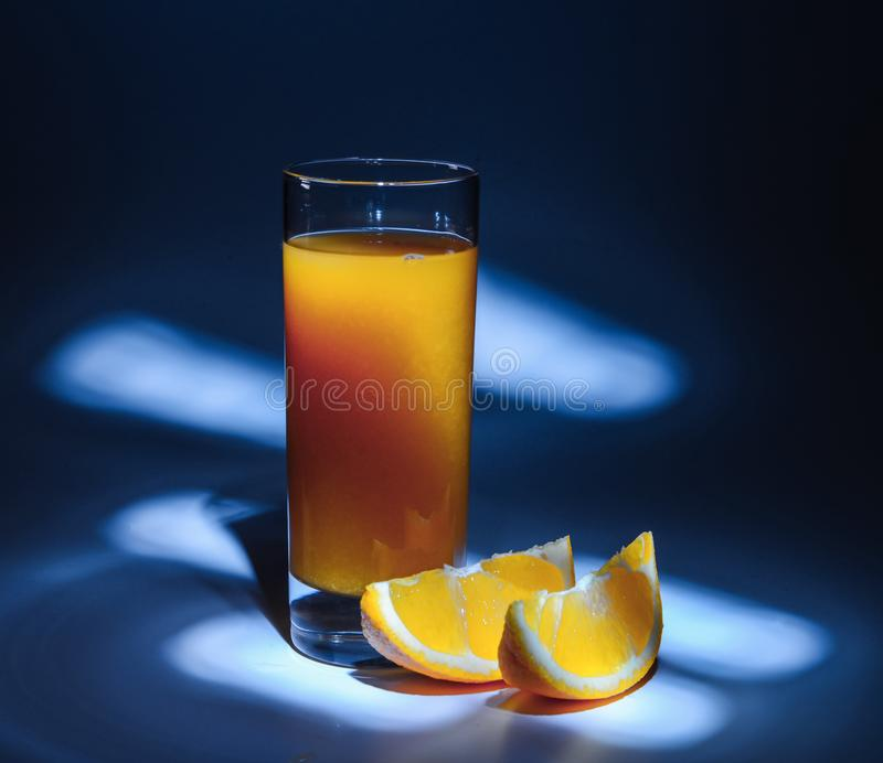 A glass of fresh orange juice and slices of orange on a blue background with backlight. In the dark tonality. Side view stock images