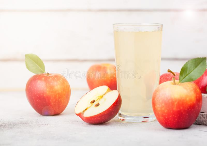 Glass of fresh organic apple juice with braeburn pink lady apples in box on wooden background with sun light stock image