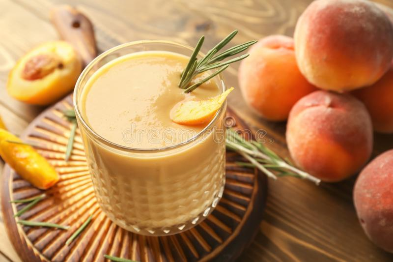 Glass with fresh peach smoothie on wooden board royalty free stock images