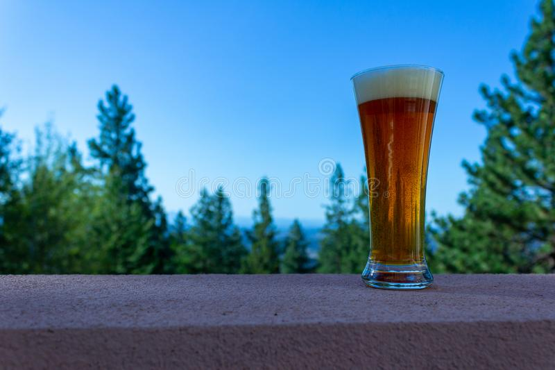 Glass of fresh poured beer sitting on a ledge on a clear day. Copyspace provided. Fresh glass of beer with foam sitting on a ledge with a view. copyspace stock photos