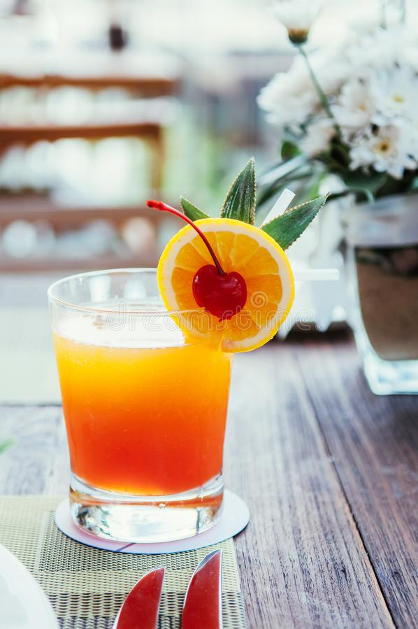 A glass of fresh orange juice with orange slice and pickled cherry stock image