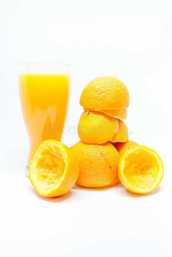Glass with fresh squeezed orange juice and half orange peels on white healthy life concept royalty free stock image