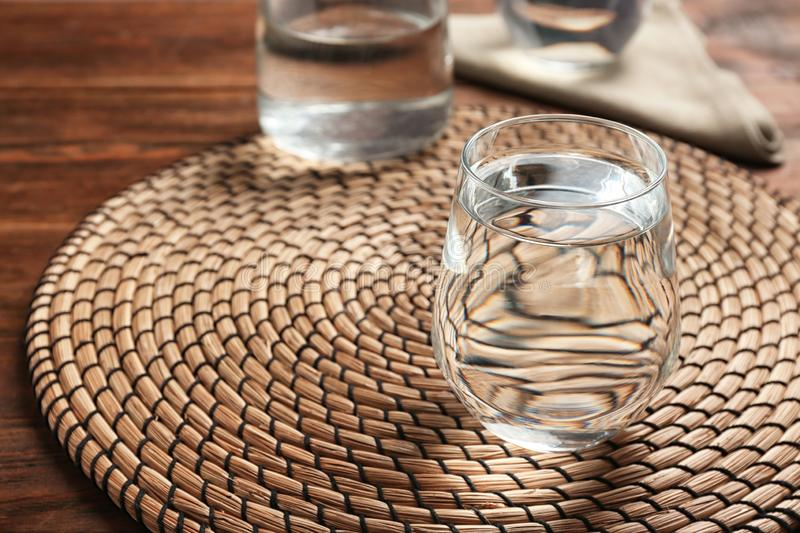 Glass with fresh water and bamboo mat on wooden table stock image