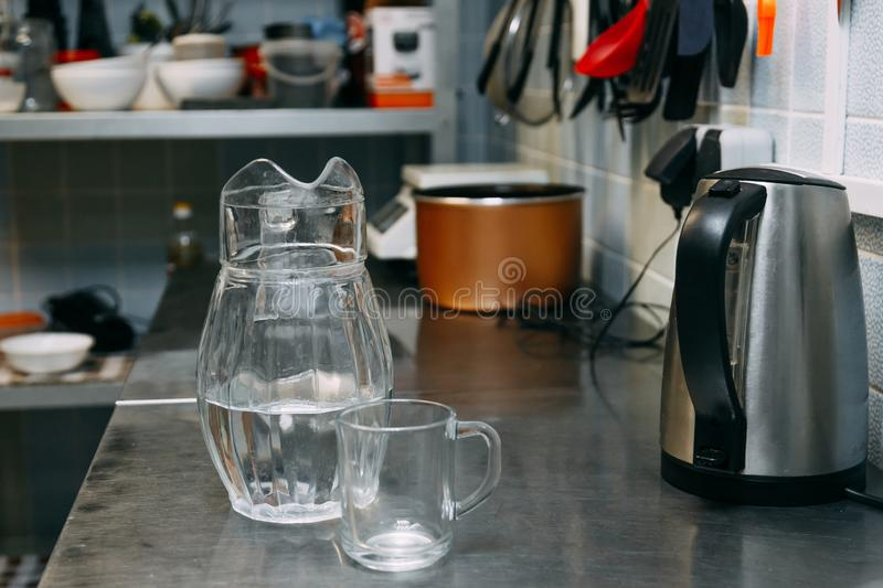 A glass of fresh water with crafin on the background of a modern kitchen. stock photos