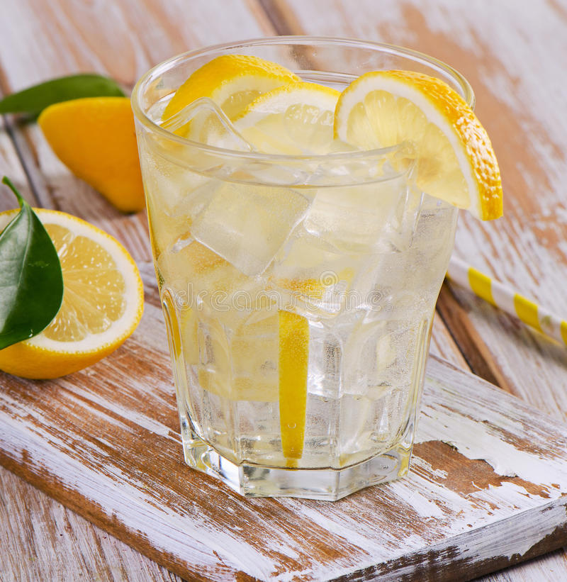 Glass of fresh water with a lemon stock photos