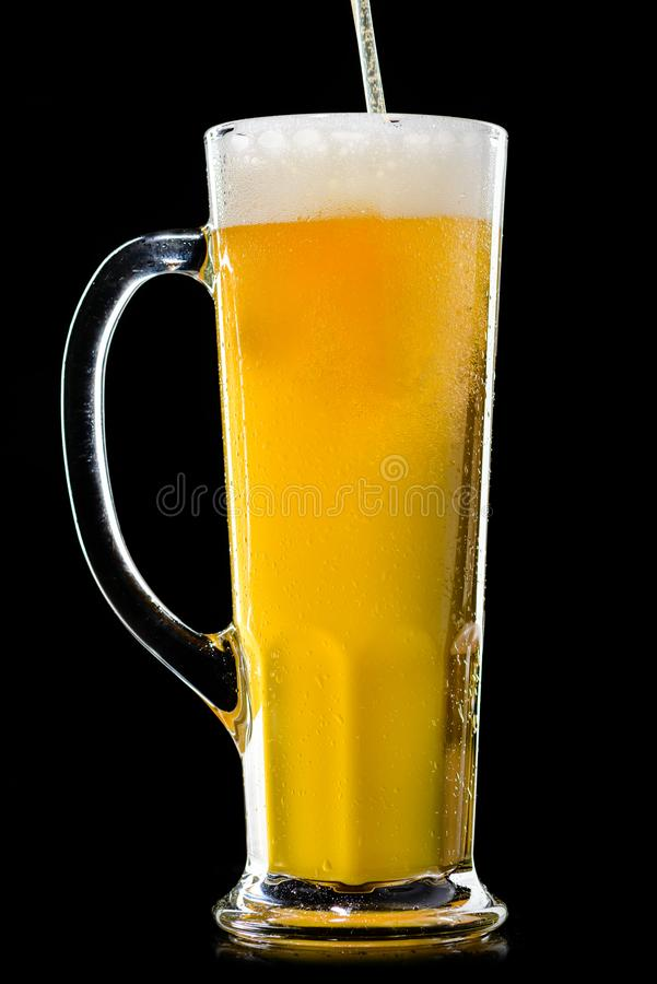 A glass of frosty fresh light unfiltered beer with straw on dark stock photography