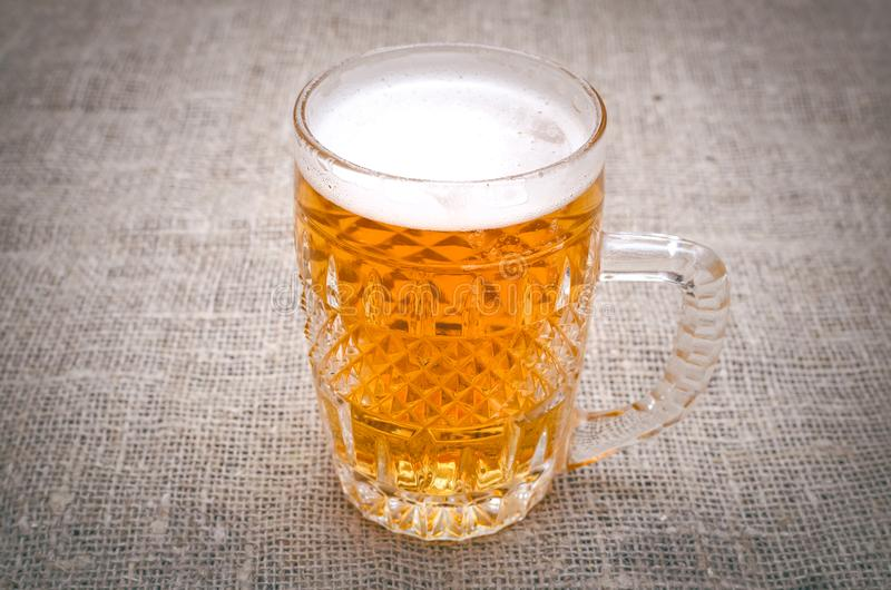 Glass of frothy light beer. Alcohol in the mug. royalty free stock photo