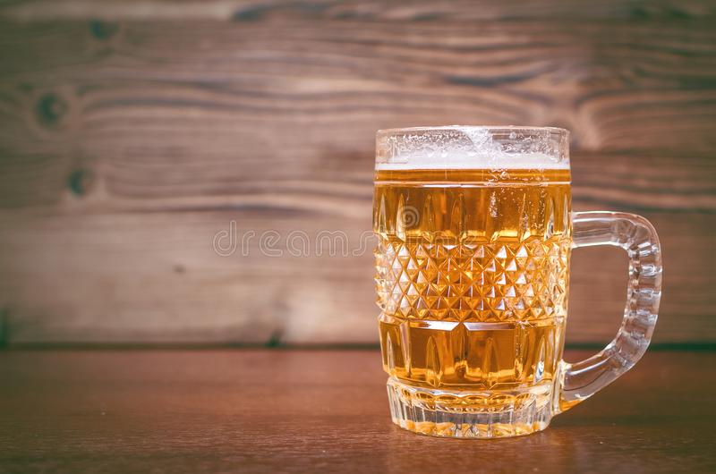 Glass of frothy light beer. Alcohol in the mug. stock photos