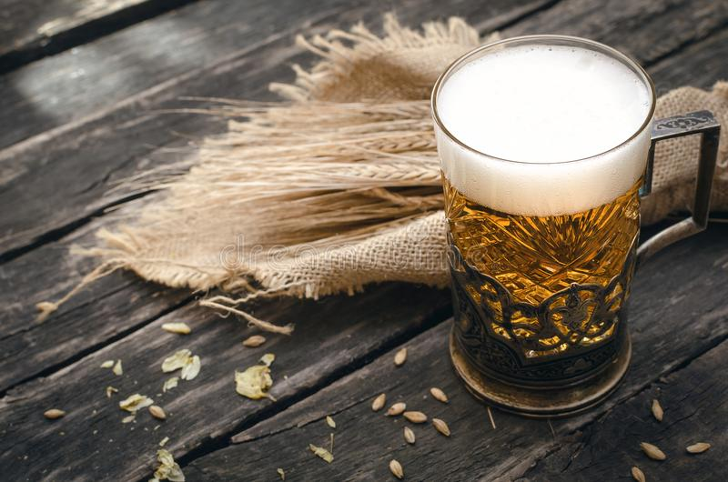 Glass of frothy light beer. Alcohol in the mug. stock images