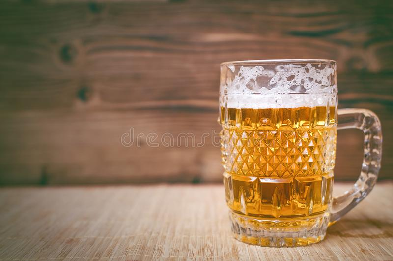 Glass of frothy light beer. Alcohol in the mug. royalty free stock photos