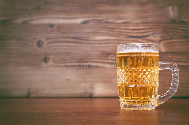 Glass of frothy light beer. Alcohol in the mug. stock photo