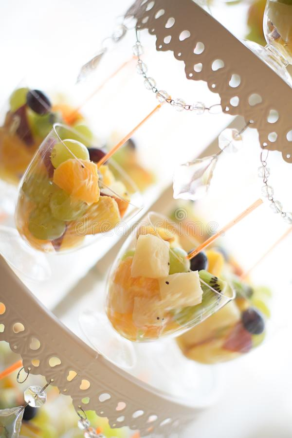 Glass fruit cups set on a tiered cake display, assortment of sweets and cakes at a candy buffet. Tasty dessert variety catered for a birthday party, wedding stock photo