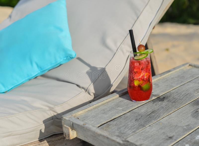 Glass of fruit juice on a beach table. In summer day royalty free stock images