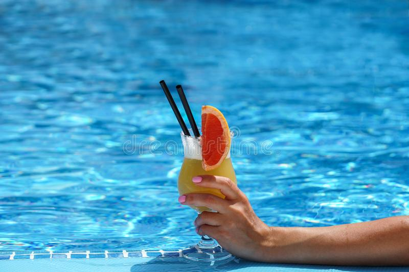 Glass of fruity cocktail in a woman s hand on pool water background stock photos