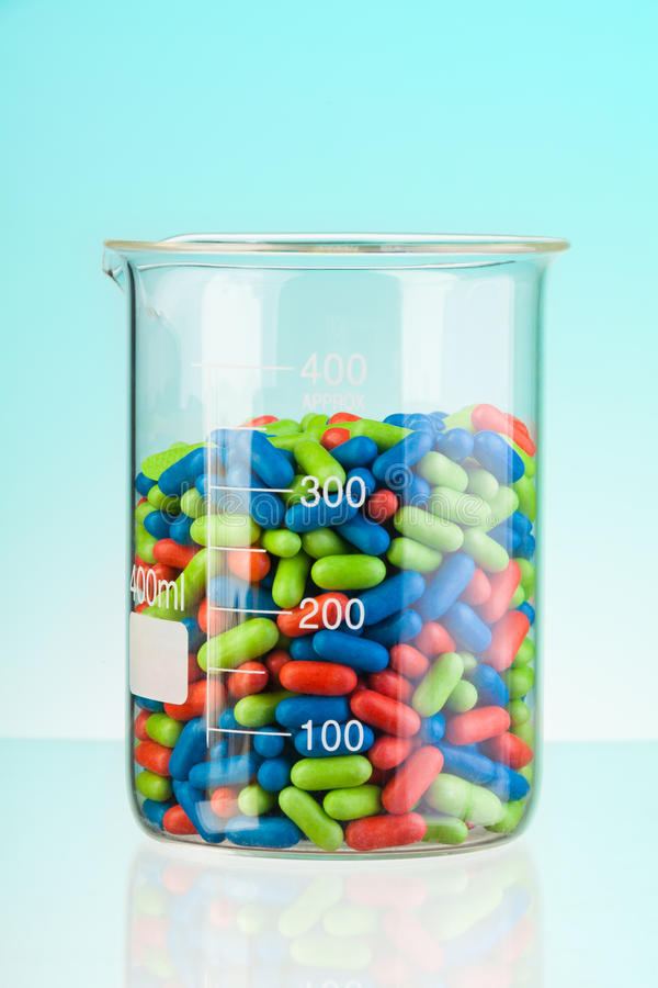 Glass full of color drugs stock photography