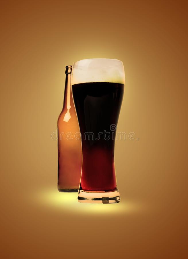 A glass full of dark beer and an empty bottle behind. Artistic processing stock photo