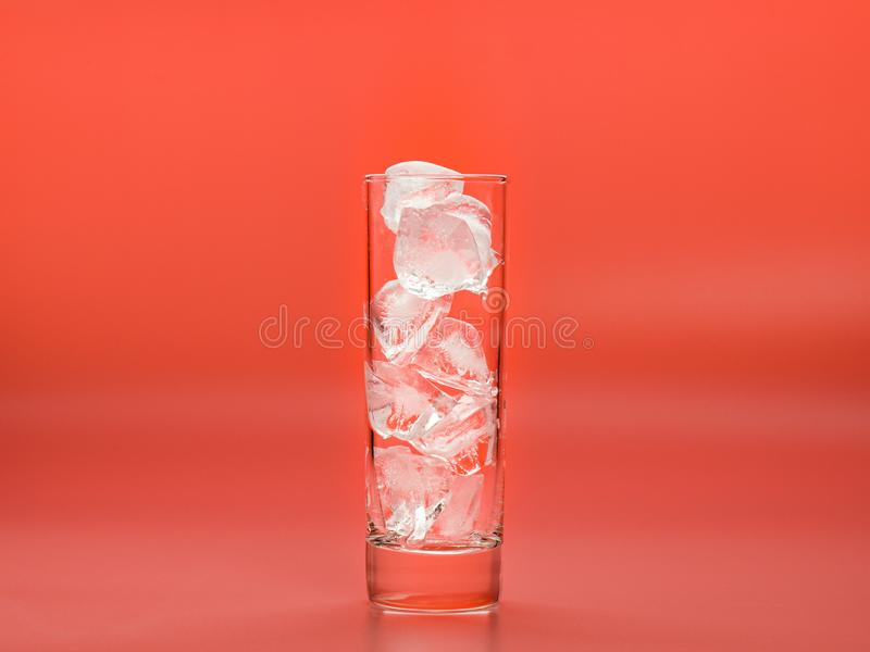Glass full of ice cubes on pink background, close up view. Pieces of solid water in glass photographed while melting. Down. Selective soft focus. Blurred royalty free stock photo