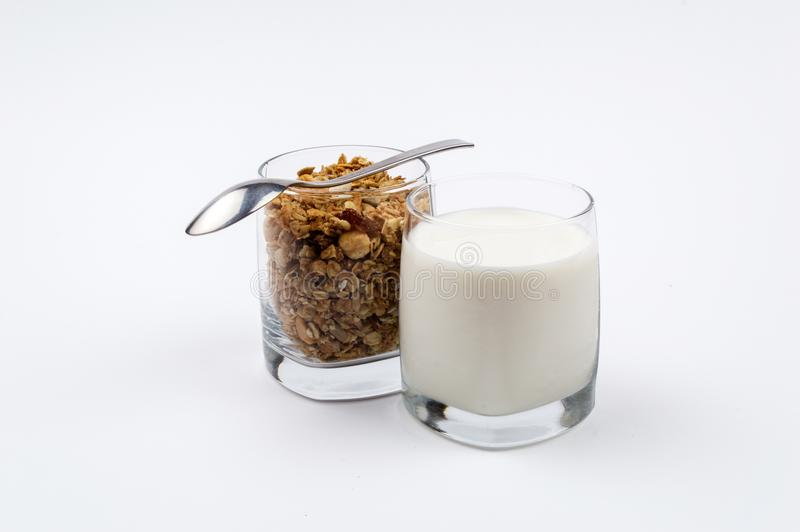 A glass full of milk and a glass full of muesli with a stainless royalty free stock photography