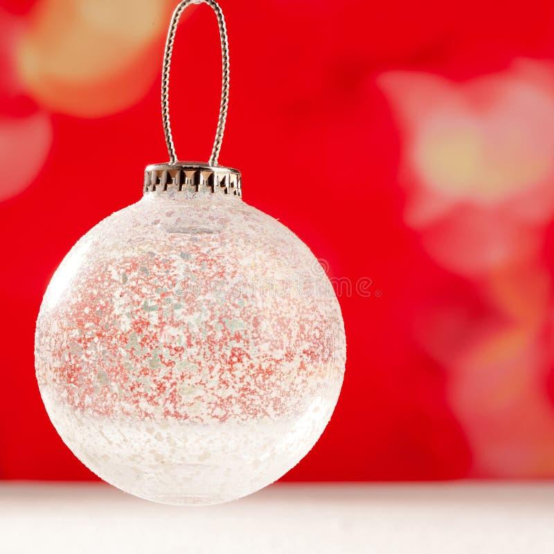 Glass genomskinlig bauble för jul på snow royaltyfri fotografi