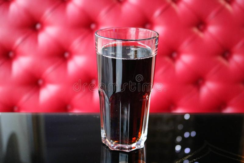 A glass glass with a brown, sweet, cold, carbonated drink on a table in a cafe in the evening on the background royalty free stock images