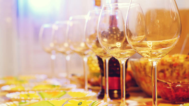 Glass glasses on a table in a restaurant, banquet table, glasses of wine stage lighting. royalty free stock photo