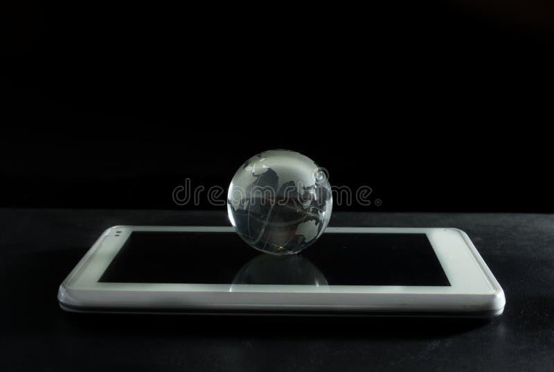 Glass globe on computer tablet. stock photos