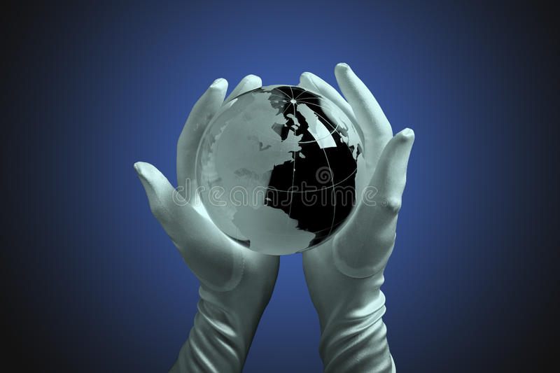 Glass globe in hand with light. Glass globe in hand with gloves, gradient blue background. Concept of protection, ecology, power stock photo