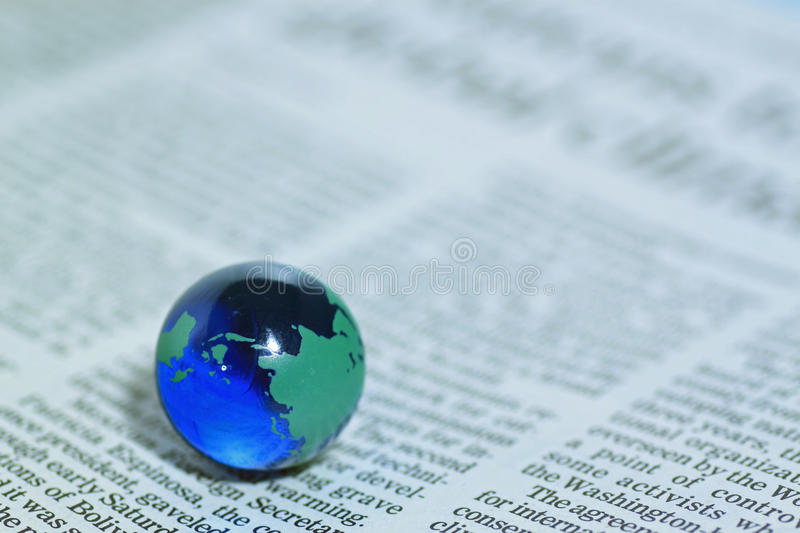 Glass globe over newspaper royalty free stock photography