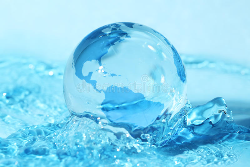 Glass globe in water. Glass globe in blue water stock photography