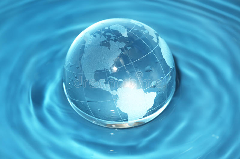 Glass globe in water. Glass globe in blue water royalty free stock image