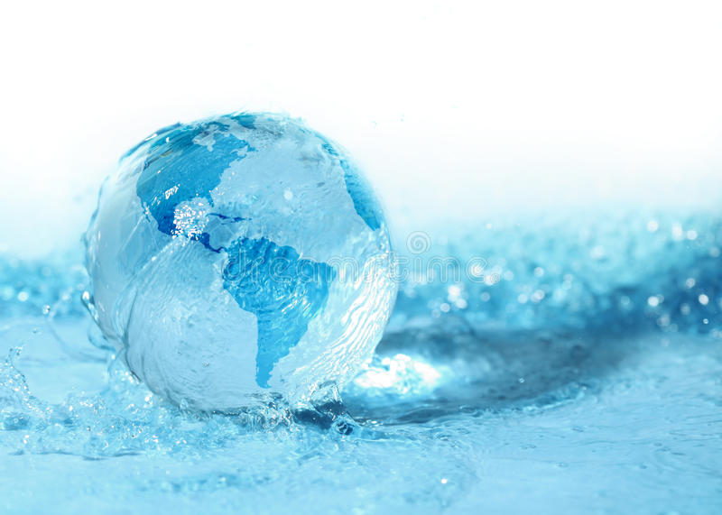 Glass globe in water. Glass globe in blue water royalty free stock photography