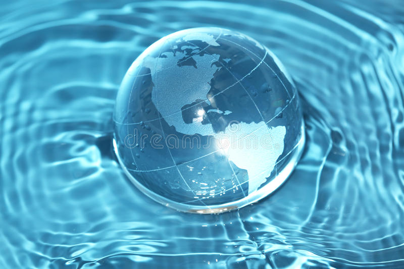 Glass globe in water. Glass globe in rippling water royalty free stock photo