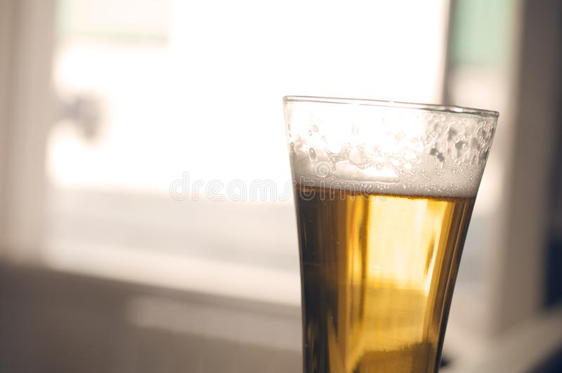 Glass of golden beer with foam on blurred background cinematic color grading. Glass of golden beer with foam on blurred background, cinematic color grading stock image