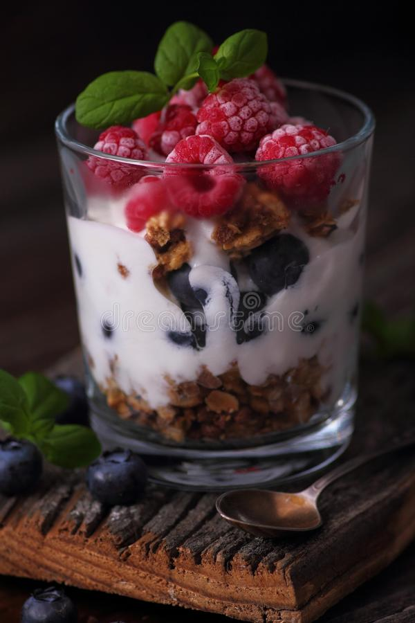 Glass with granola, yogurt and frozen fruits royalty free stock photos