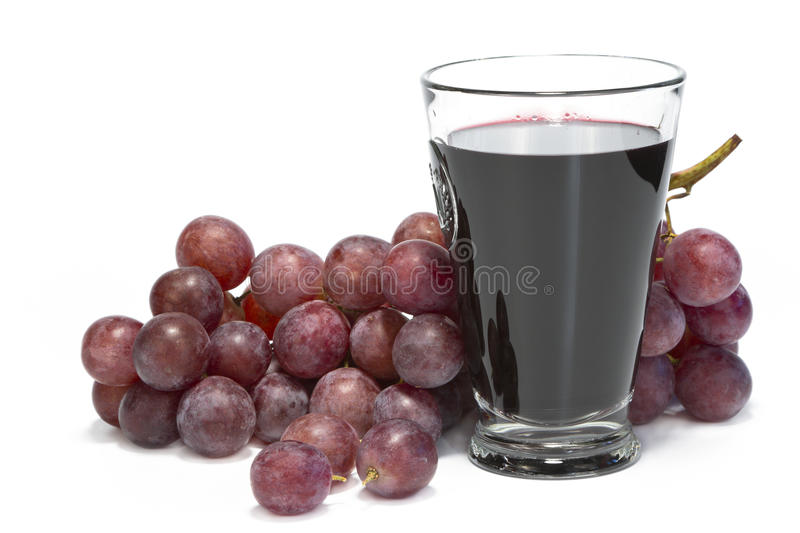 A glass of grape juice and bunch of grapes. stock images