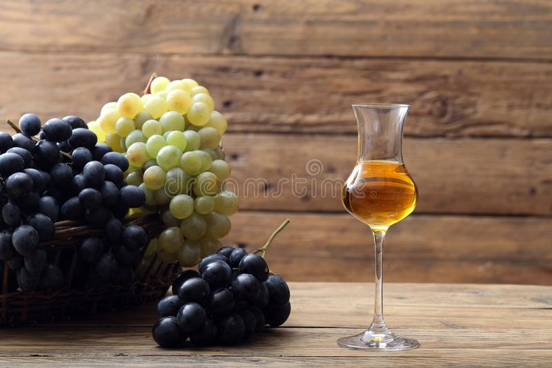 Glass of grappa on rustic table. Background stock image