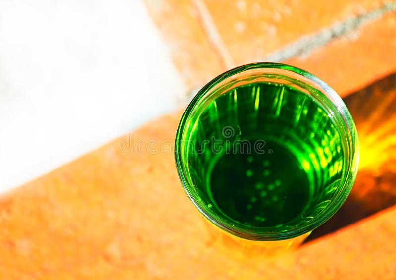 Glass of green acid soda object background. Horizontal orientation vivid vibrant bright color spacedrone808 rich composition design concept element shape stock photography