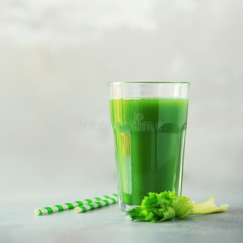 Glass of green celery smoothie on grey concrete background. Banner with copy space. Square crop. Vegan, alkaline healthy diet stock images