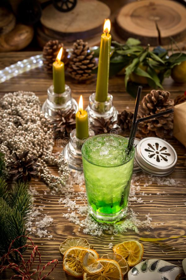 Glass of green lemon soda with ice on wooden table on christmas decorated background stock images
