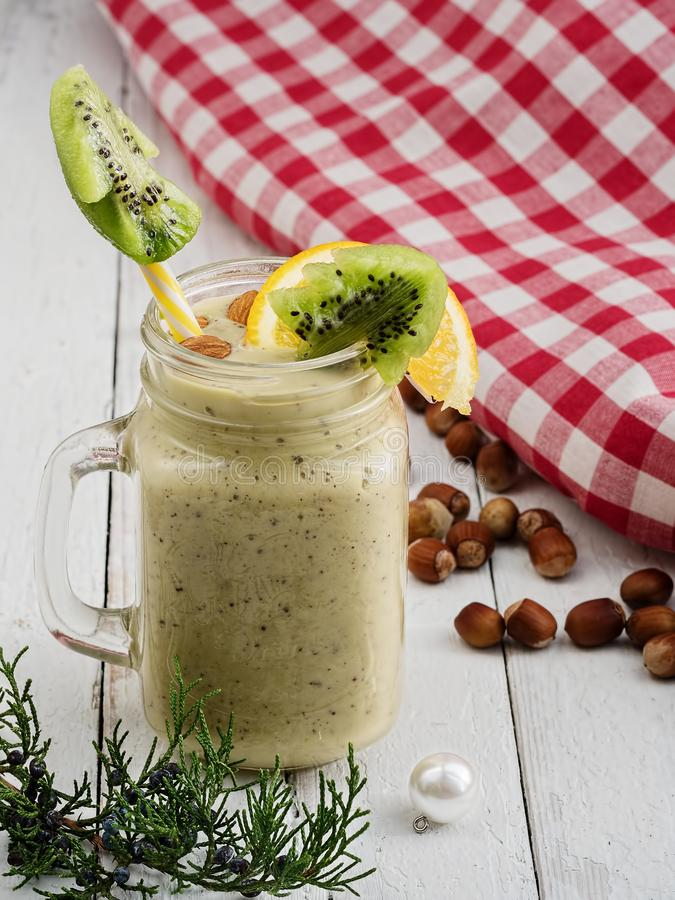 A glass of green smoothie with banana, almond milk, kiwi and matcha. The concept of vegetarian and healthy eating. Close-up. The stock photos