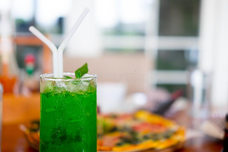 Glass with green soda aerated water. Drink for cool down in hot summer stock photo