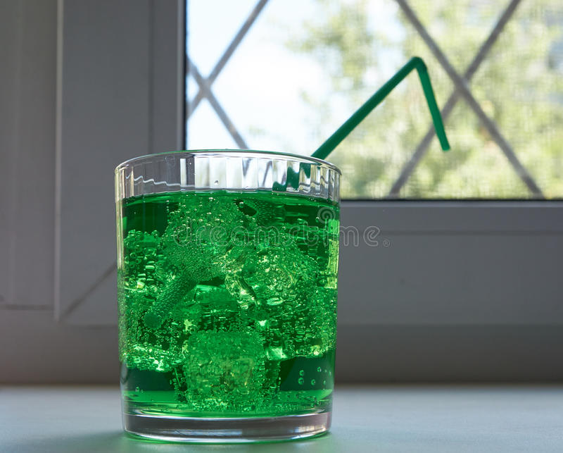 Glass with green soda aerated water. With ice and drinking straw near window. drink for cool down in hot summer royalty free stock image
