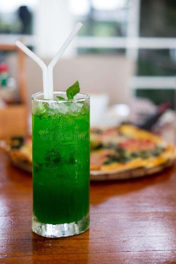 Glass with green soda aerated water. On pizza background stock photos