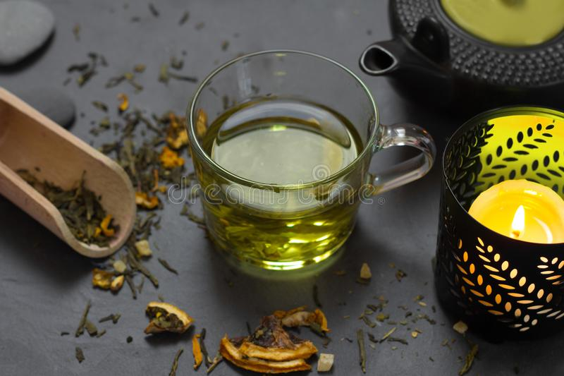 Glass of tea with candle still life. Glass of green tea with candle still life stock photography