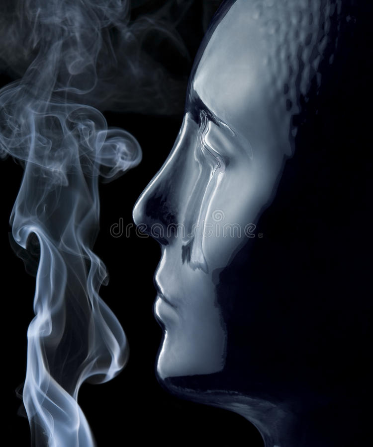Glass head and smoke. Translucent reflective human head made of glass and smoke in black back stock images