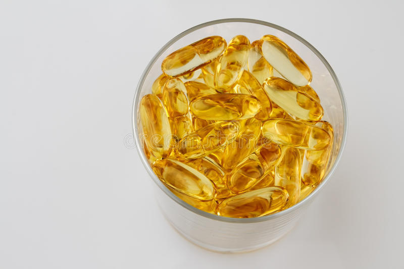 Glass of health with fish oil capsules stock photo