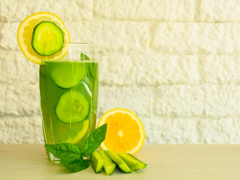 A glass of healthy green juice from cucumber and lemon decorated with basil leaves. Concepts diet. Useful summer refreshing drink royalty free stock photos