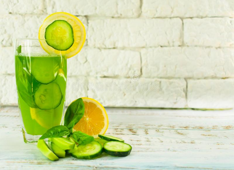 A glass of healthy green juice from cucumber and lemon decorated with basil leaves. Concepts diet. Useful summer refreshing drink royalty free stock photo