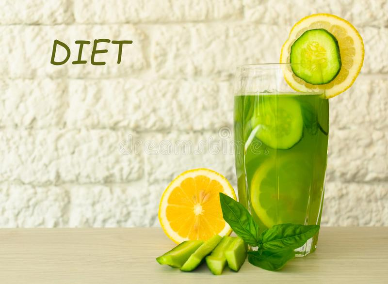 A glass of healthy green juice from cucumber and lemon is decorated with basil leaves. Concepts diet. Useful summer refreshing dri royalty free stock image