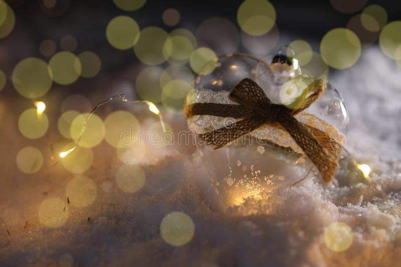 Glass heart and Christmas lights on snow against blurred background, space for text. Winter decor stock images